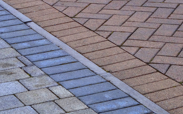 Photo showing a couple of driveways side by side, where different blocks and bricks have been laid.  The drive on the left has opted for an irregular mix of pale blocks, while the drive on the right has chosen red bricks, laid in a herringbone pattern.