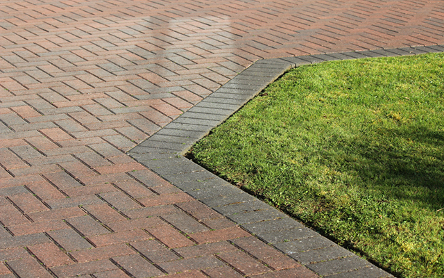 Photo showing a driveway made from brick paving, where the red bricks have been laid out to create a herringbone pattern.  The paving is edged by a row of darker brown bricks, which separate the drive from the green front lawn.
